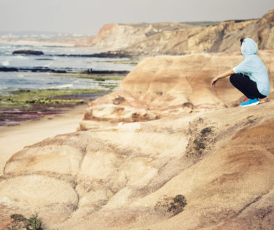 Woman wearing athletic wear and running shoes sitting on top of a cliff looking out into the ocean after a run