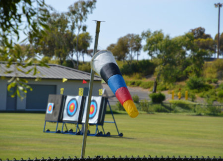 Archery wind sock blows in the wind and nearby targets are seen in the distance at the Roadrunner Archery Club archery range